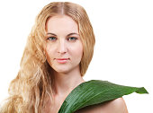 Beauty young blond woman with green leaf isolated on white