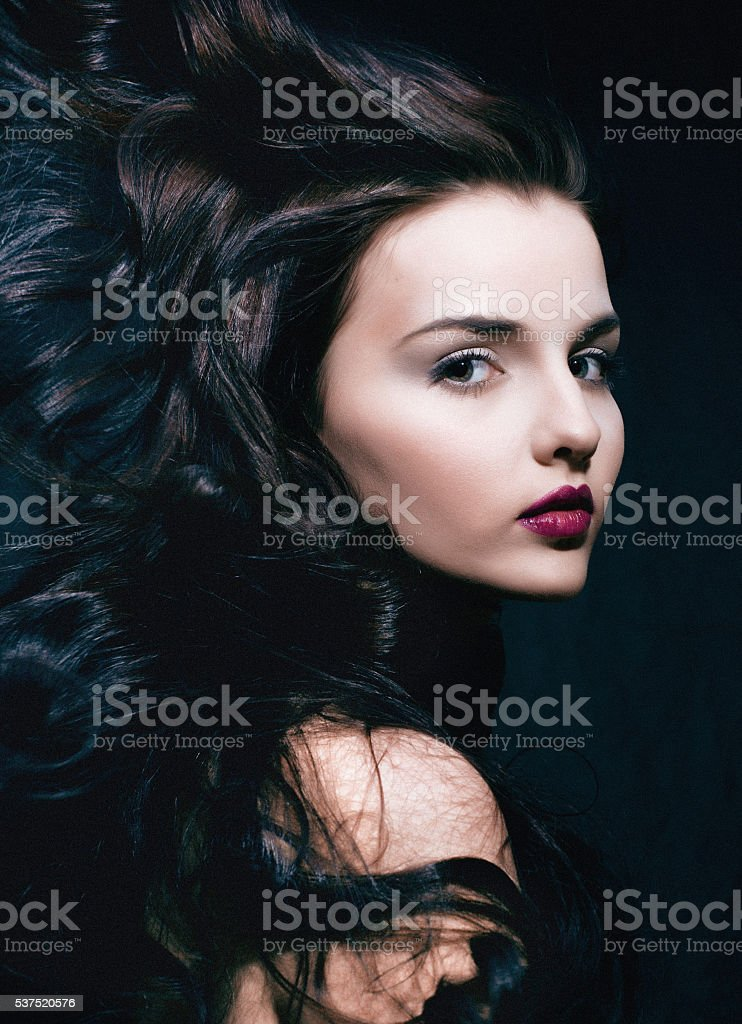 beauty young brunette woman with curly flying hair, femme fatal stock photo
