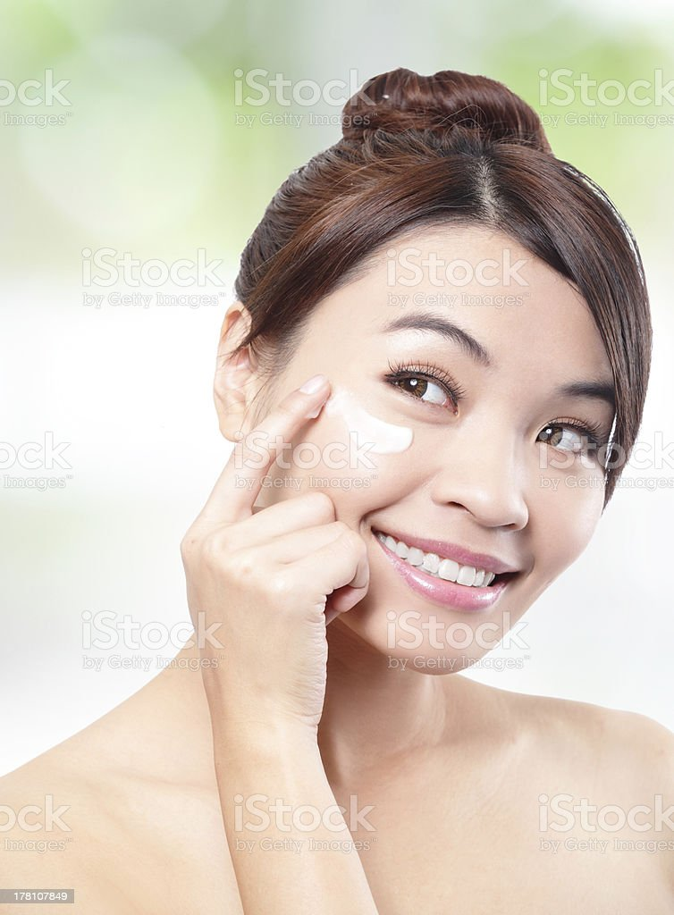 Beauty young woman applying cosmetic cream royalty-free stock photo