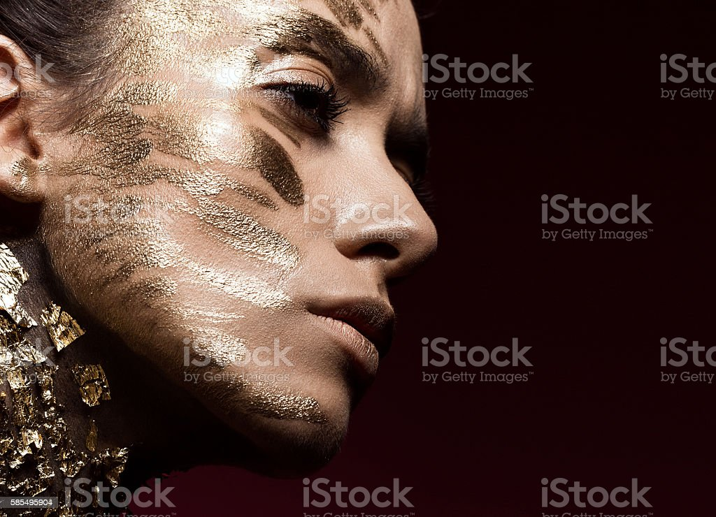 Beautyful girl with gold glitter on her face. Art image stock photo