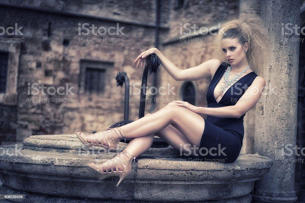 Beautyful woman sitting on a fountain wearing a designer dress stock photo