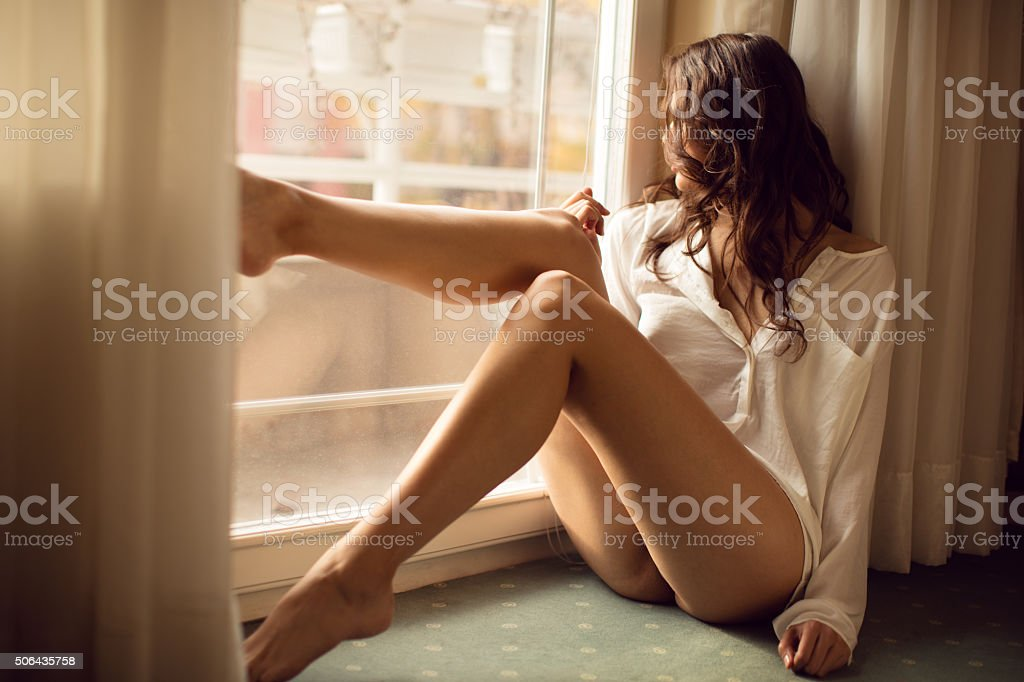 Beautyful young blond woman sitting next to the balkony door stock photo