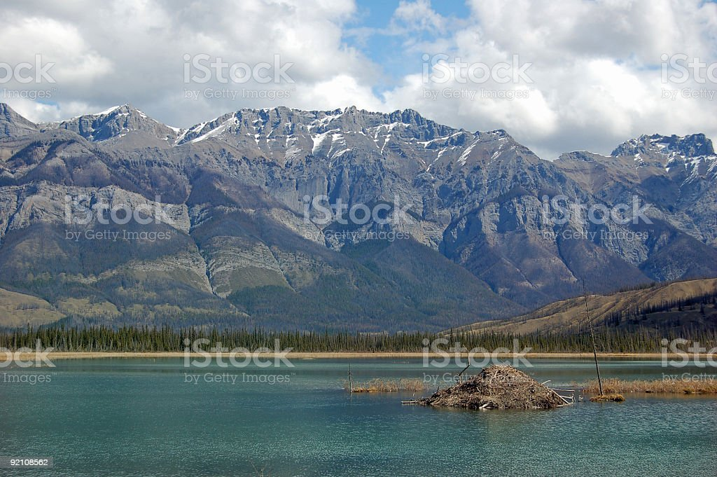 Beaver Lodge on Mountain Lake With Dramatic Surroundings royalty-free stock photo