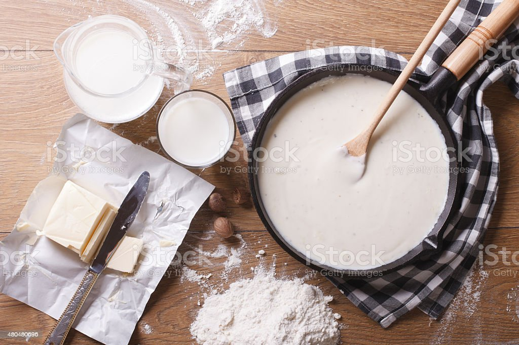 bechamel sauce in a pan and ingredients horizontal top view stock photo