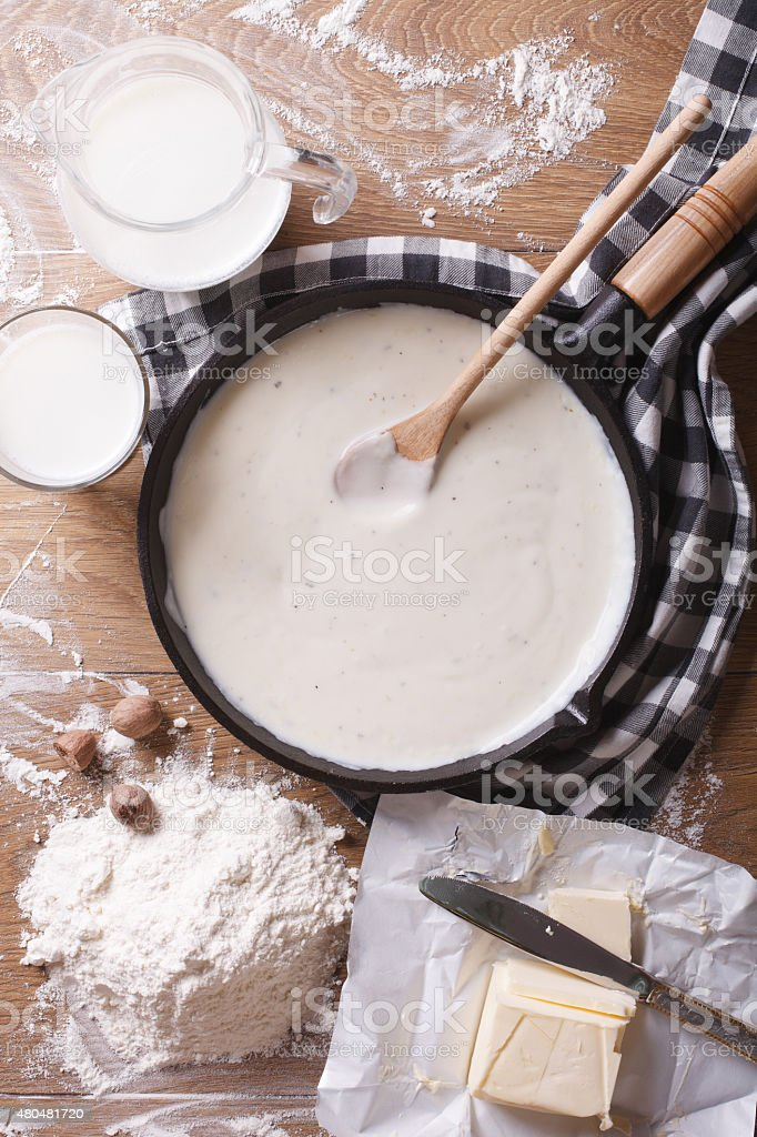 bechamel sauce in pan and ingredients vertical top view stock photo