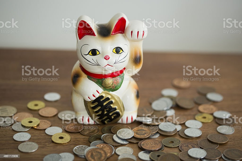 Beckoning cat and coin stock photo