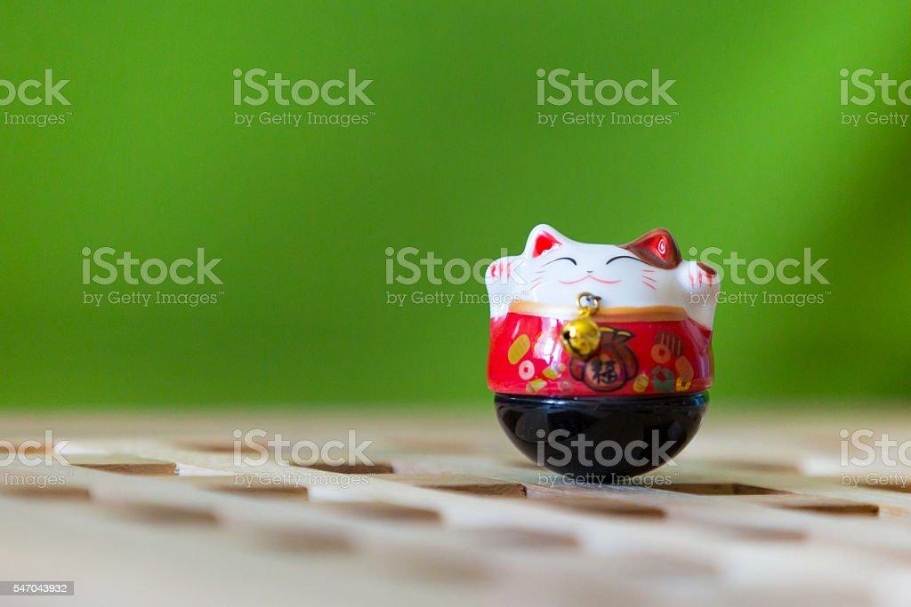 Beckoning cat, maneki neko on green background stock photo