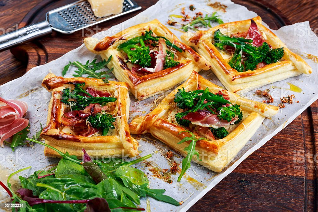 Becon, soft chees and tenderstem broccoli tips puff pastry tarts. stock photo