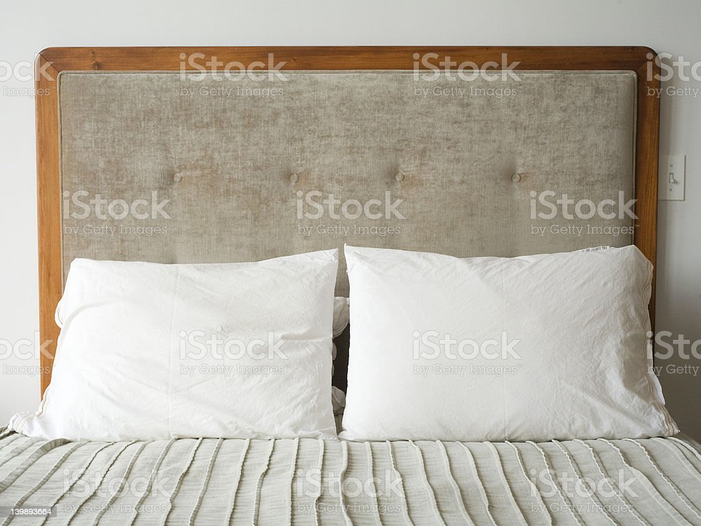 bed and head board with two pillows on royalty-free stock photo