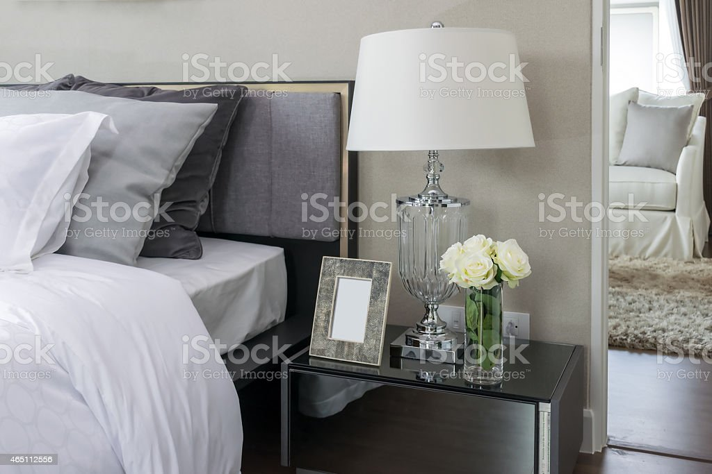 bed and pillows with white lamp on bedside table stock photo