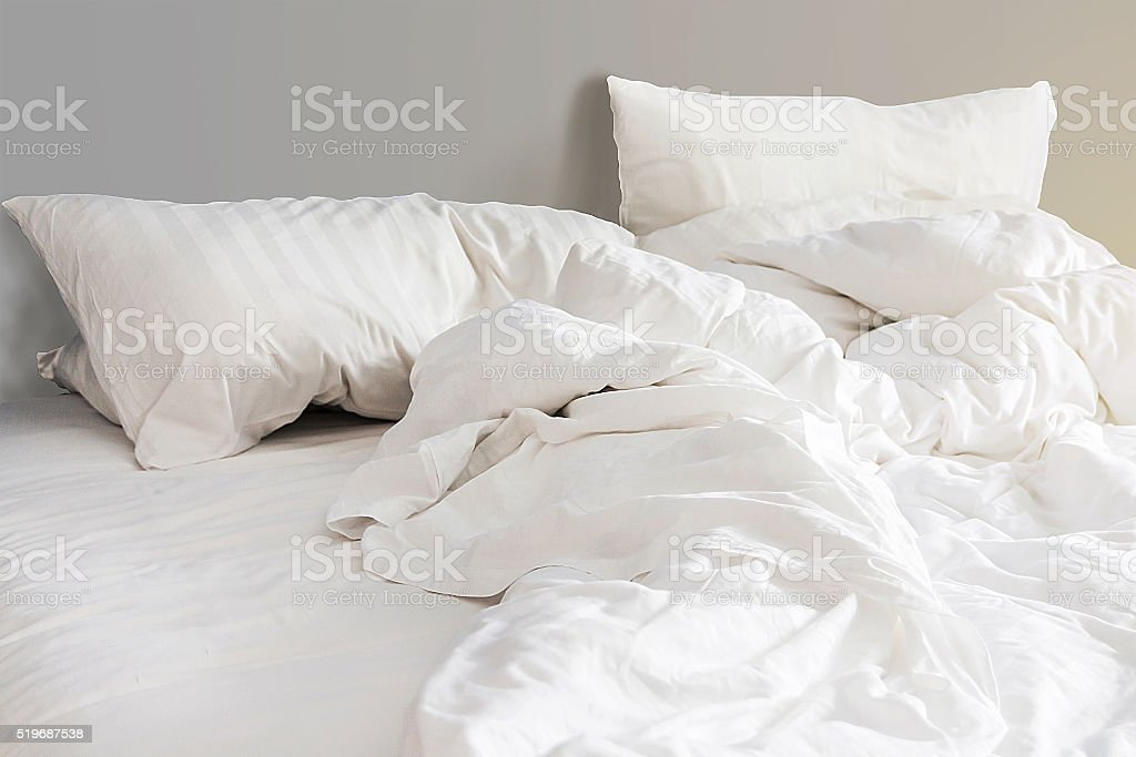 bed and white pillows with wrinkle blanket in bedroom stock photo