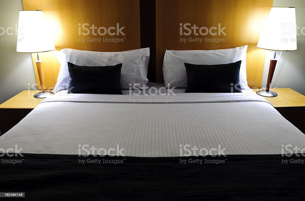 Bed clean made hotel linen two lamps stock photo