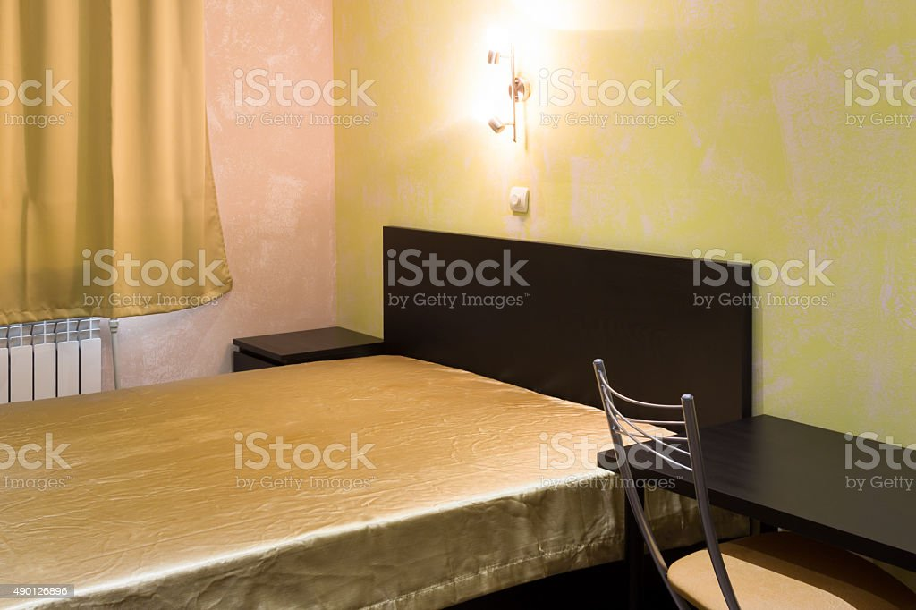 bed in a bedroom in shades of yellow stock photo