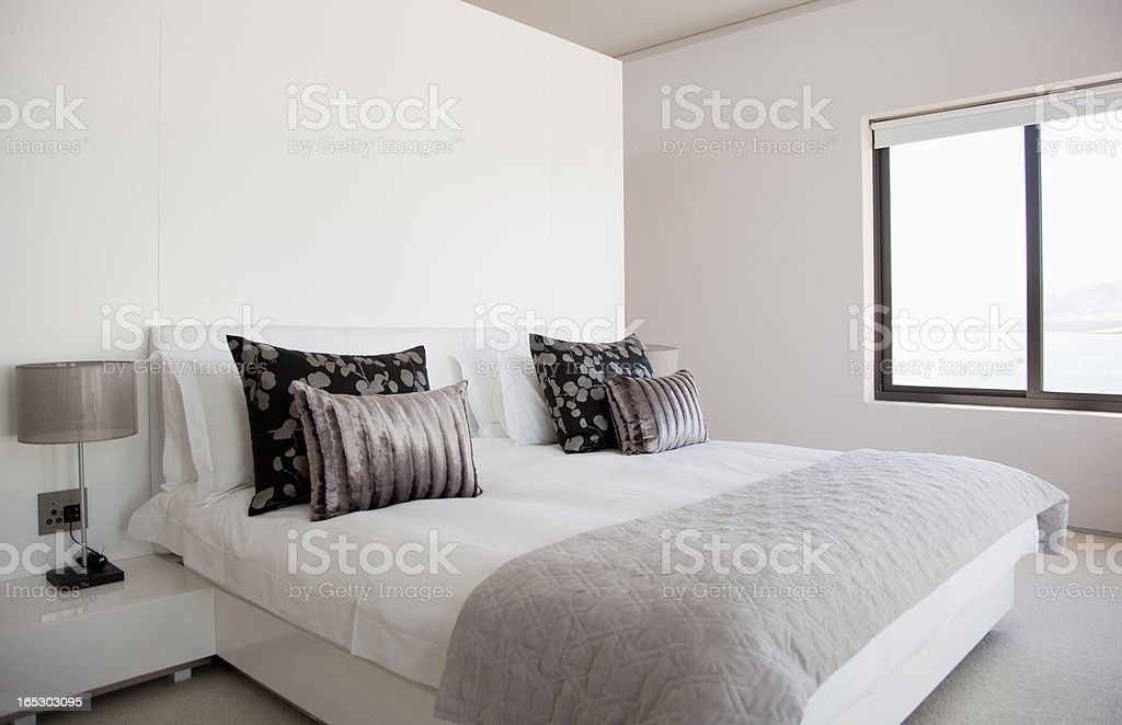 Bed in modern bedroom stock photo
