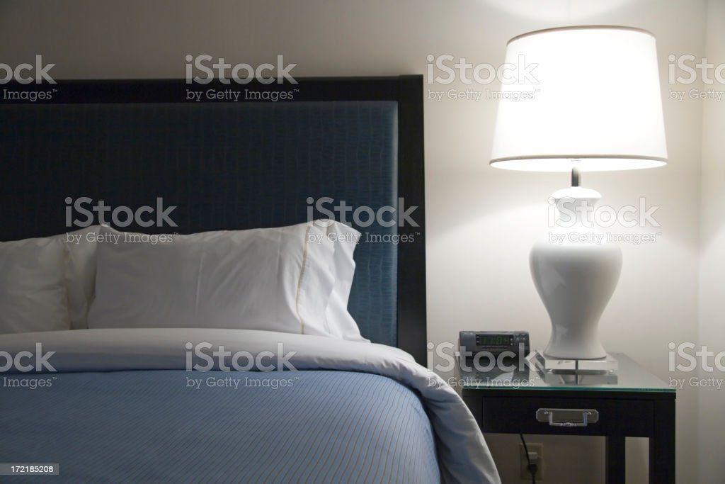 Bed of modern hotel with blue accents next to a lot lamp royalty-free stock photo