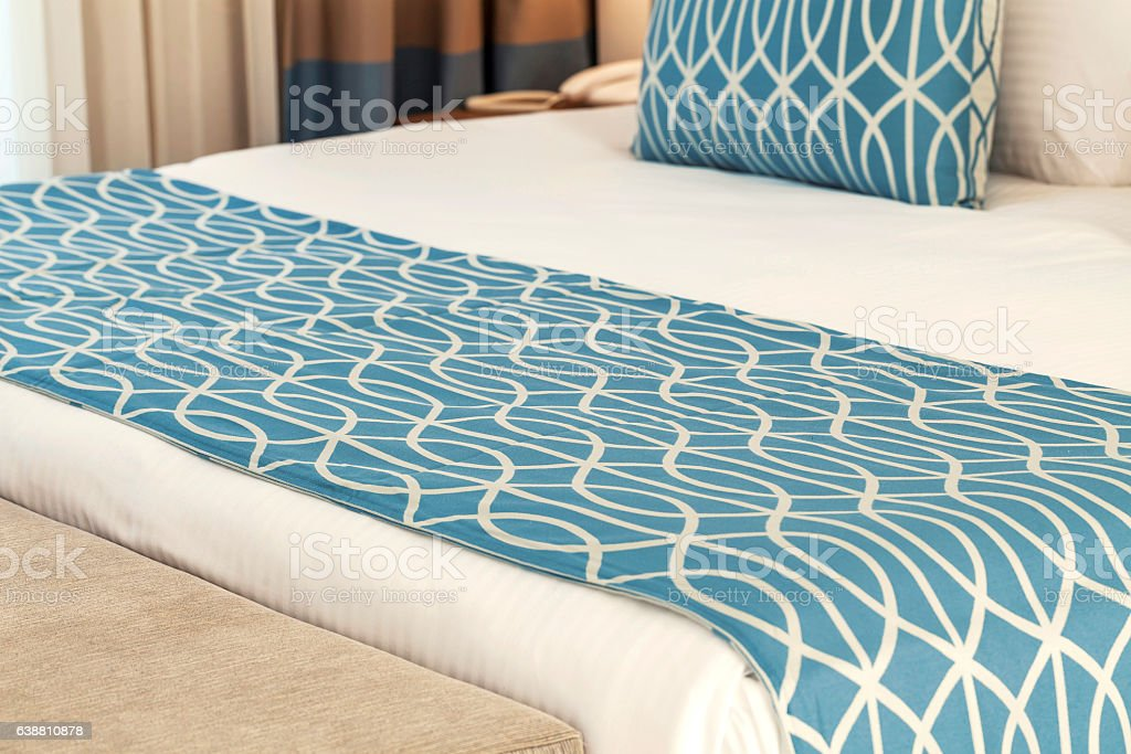 Bed runner and pillow on bed stock photo