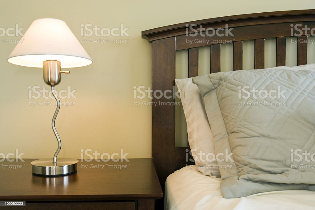 Bed, side table and lamp in modern bedroom suite  royalty-free stock photo
