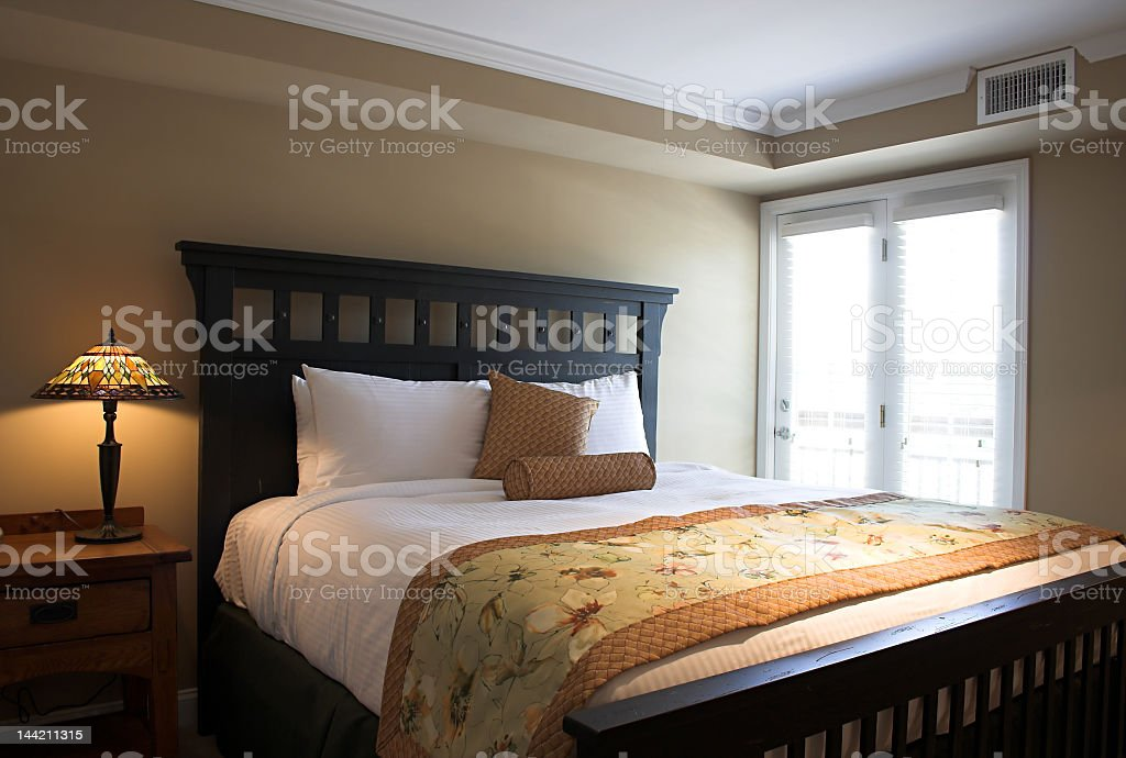 Bed with a table and lamp and a bright window royalty-free stock photo