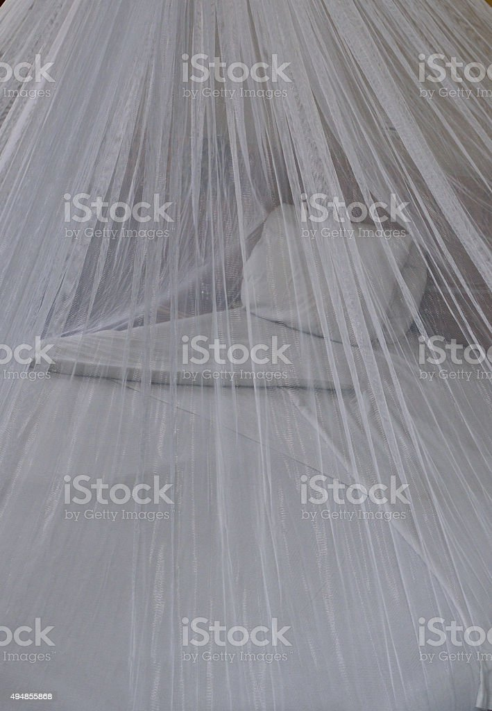Bed with mosquito net stock photo