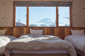 Bed with MT.Fuji view as background outside the window.