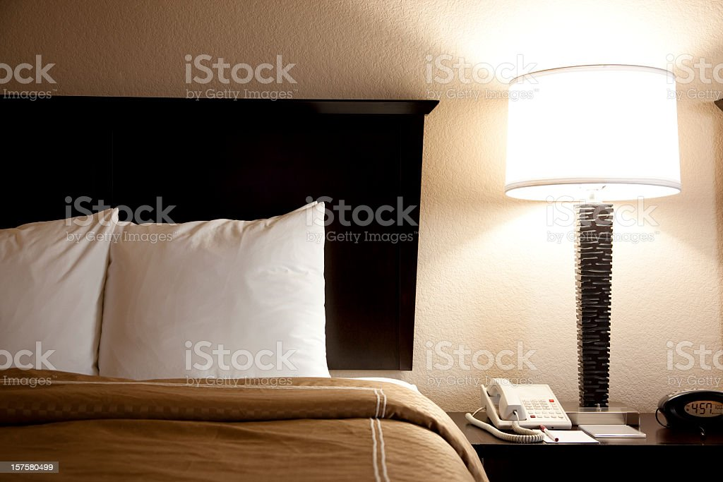 Bed with pillows, end tables and duvet. Hotel room. Lamp. stock photo