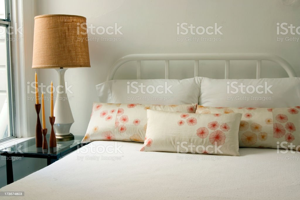 A bed with white sheets and white pillows stock photo