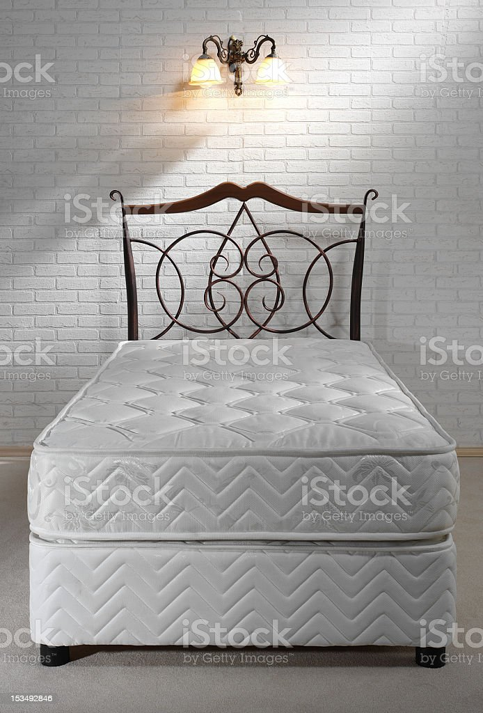 Bed without sheets on white brick wall and wall sconce  stock photo