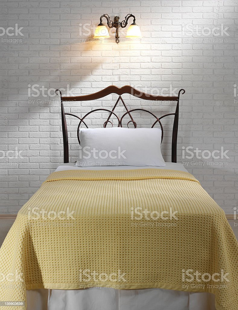 bed with yellow pique in front of white wall