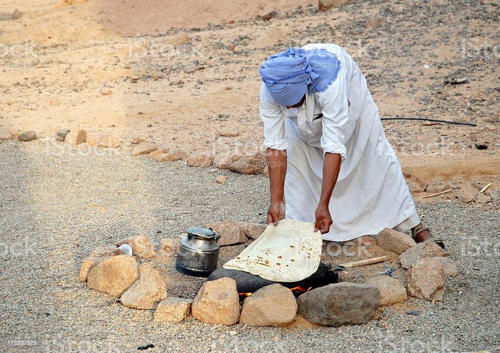 Bedouin baking bread on hot stone, Sinai Desert,Egypt stock photo