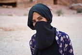 Bedouin girl, with hidden face behind veil, Petra, Jordan