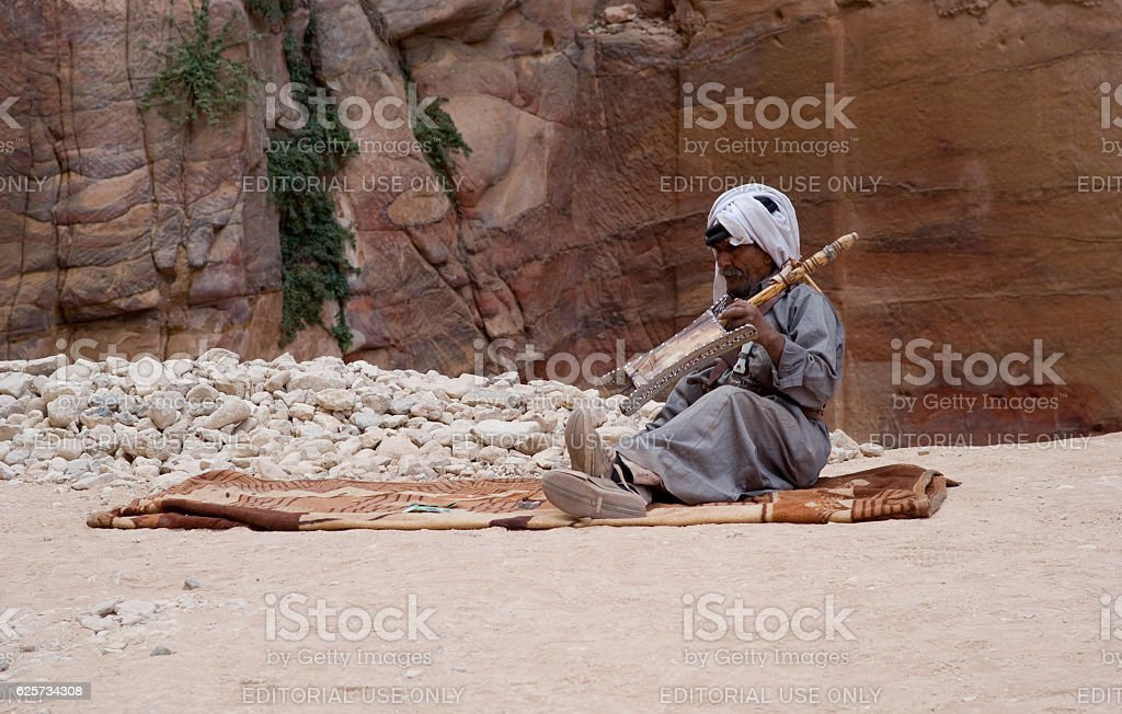 Bedouin man playing traditional instrument stock photo