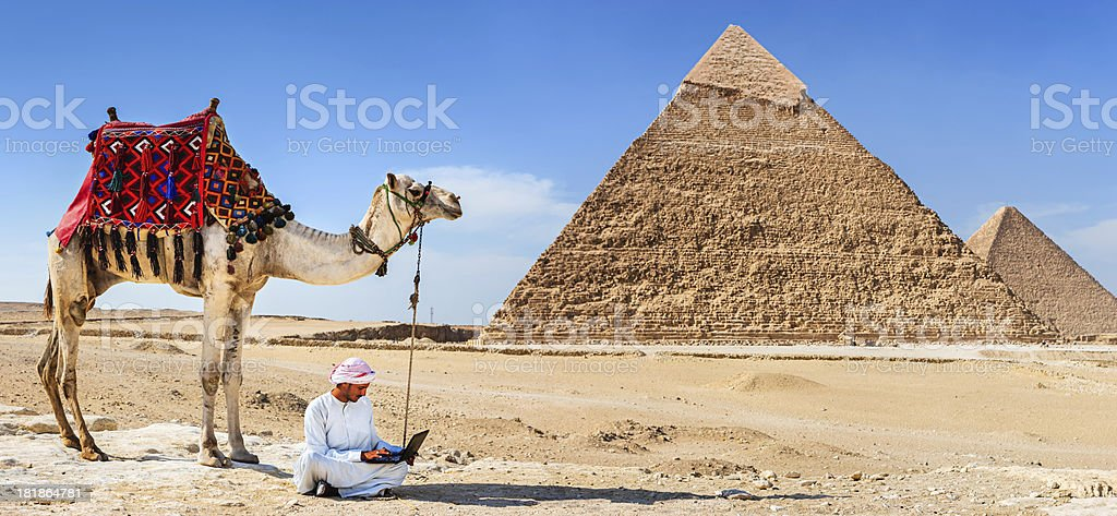 Bedouin using a laptop next to the pyramid royalty-free stock photo