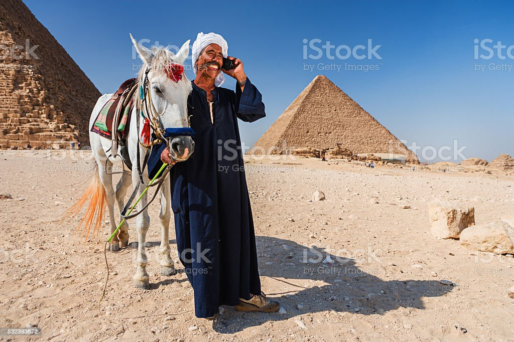 Bedouin using phone, pyramids on the background stock photo