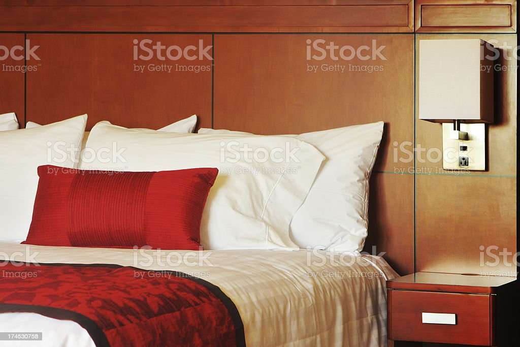 Fresh linens and bedding with wood panel headboard in a luxury resort...