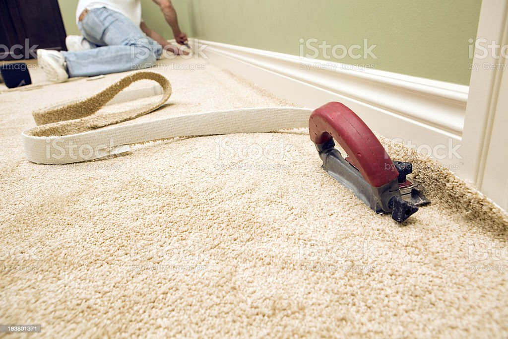 Bedroom Carpet Installation with Cutter and Worker stock photo