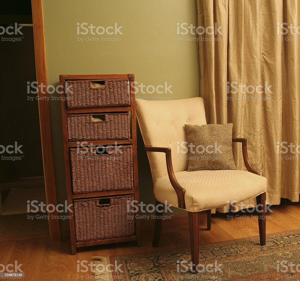 Bedroom chair next to wicker storage bins stock photo