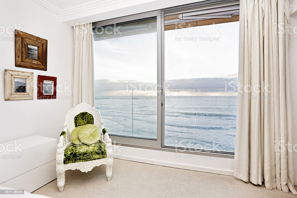 Bedroom corner with an armchair and a beautiful sea view royalty-free stock photo