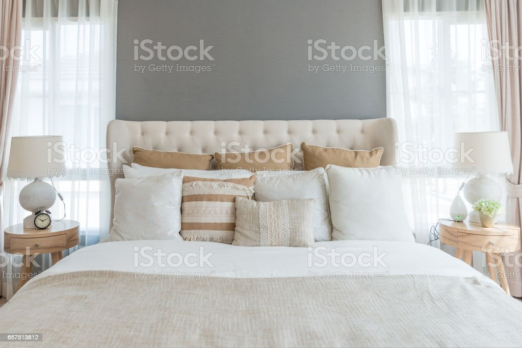 Bedroom in soft light colors. big comfortable double bed in elegant classic bedroom at home. stock photo