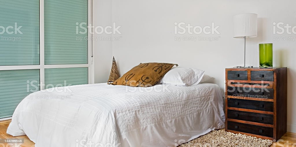 Bedroom with a white color scheme and brown accents stock photo