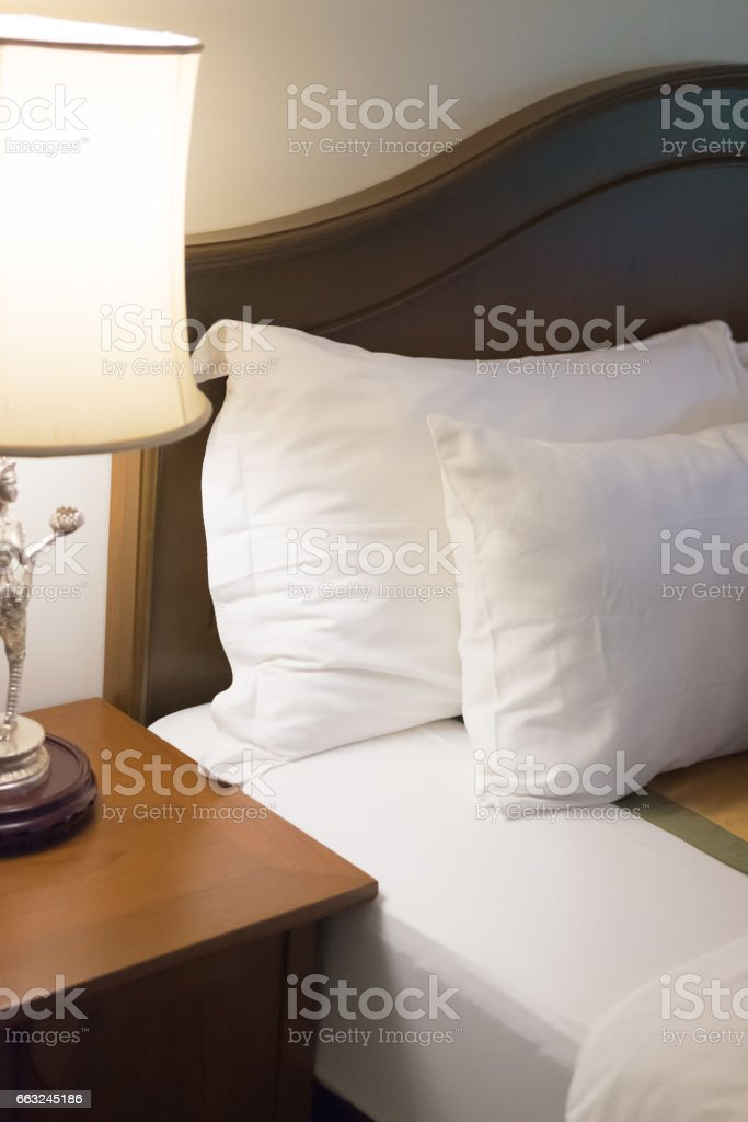 Bedroom with pillows on bed and modern  lamp on side table at home stock photo