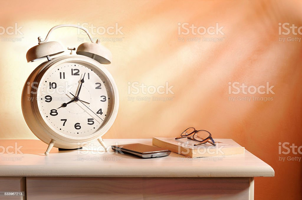 bedside alarm clock and personal belongings stock photo