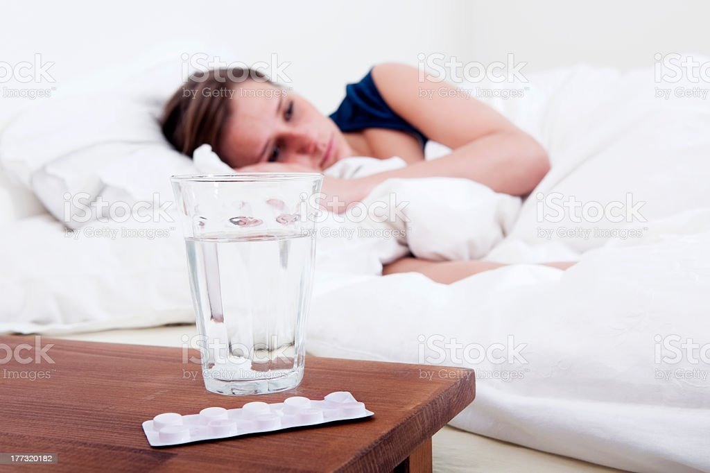 A bedside table with pills and water next to a woman in bed  stock photo