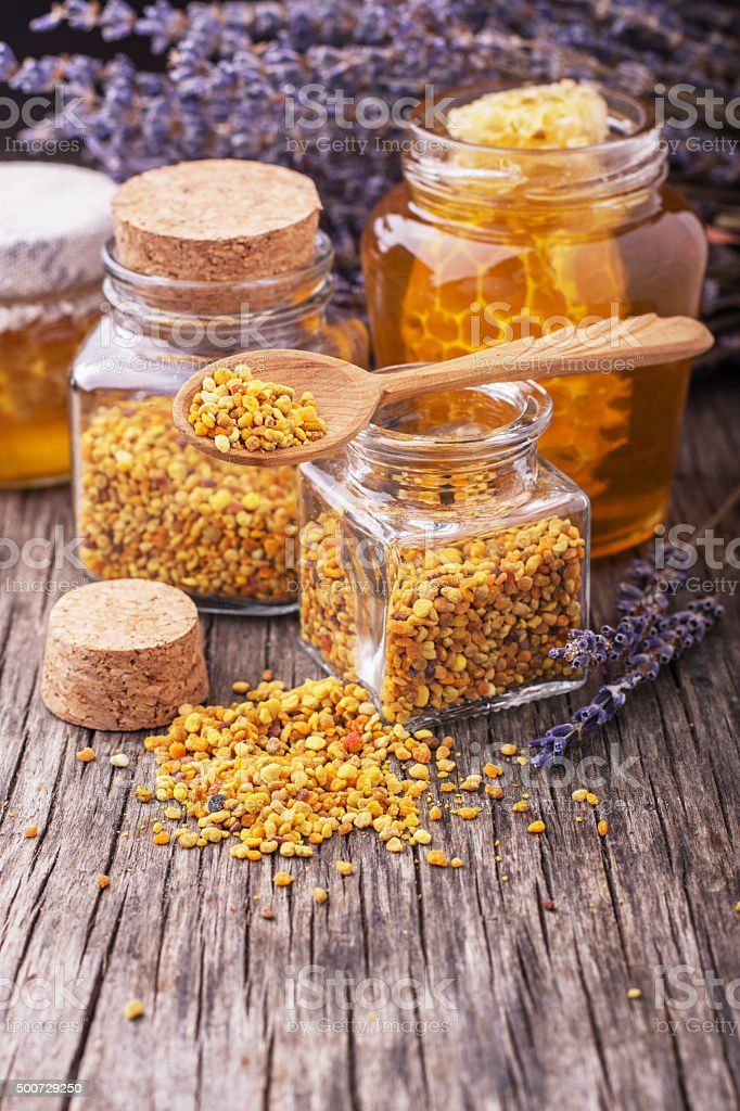 Bee pollen granules and propolis in wooden scoop stock photo
