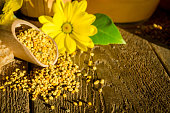 Bee pollen granules in wooden scoop, honeycombs and flowers