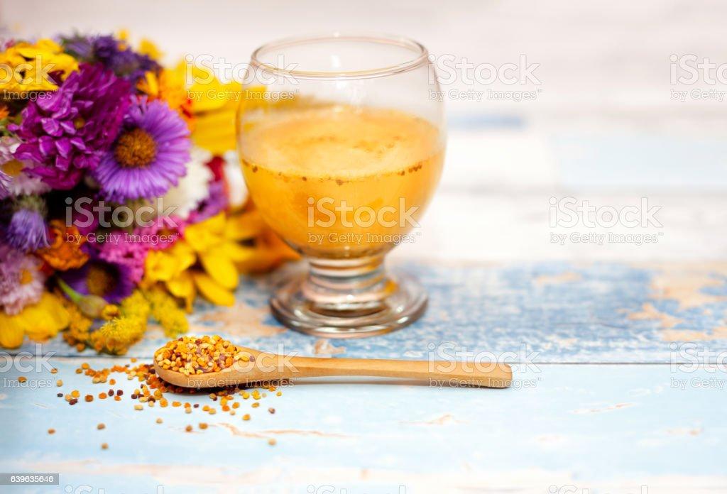 Bee pollen in wooden spoon with pollen liquid stock photo