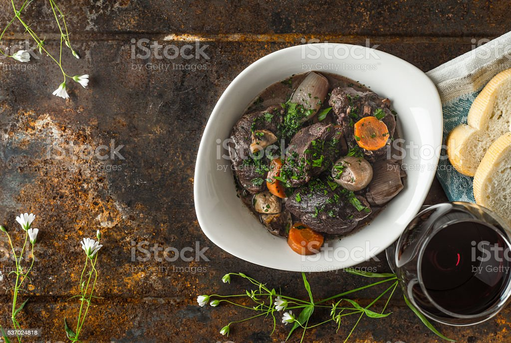 Beef bourguignon in a ceramic dish on the old metal stock photo