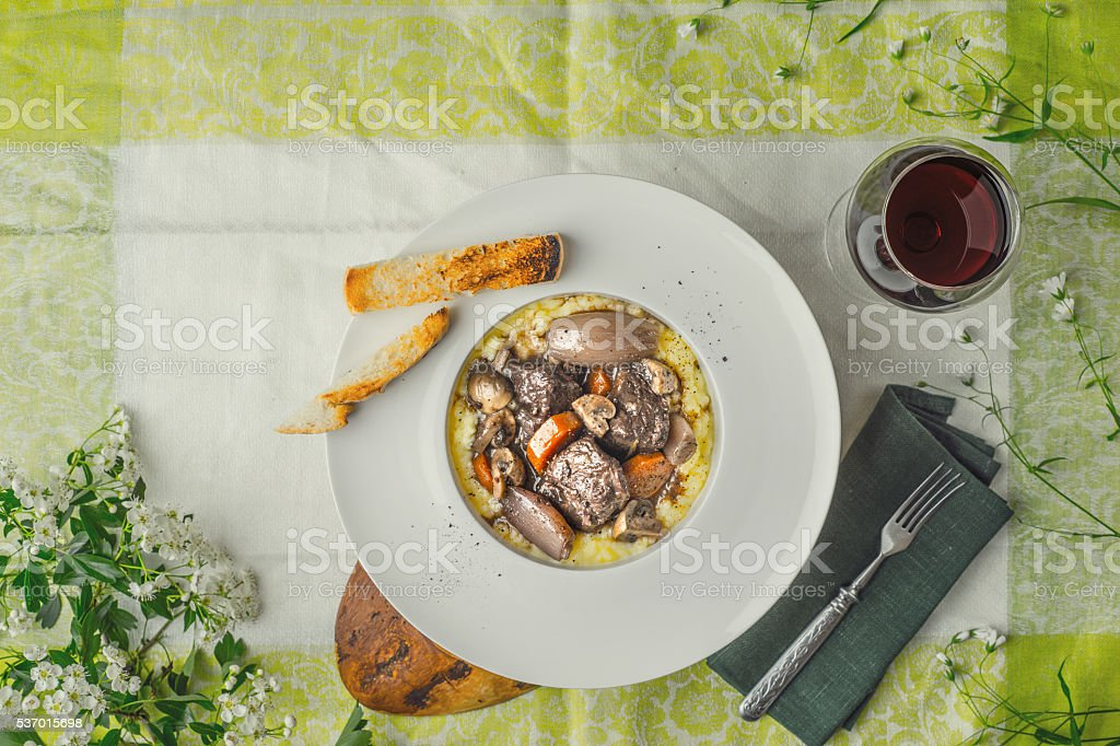 Beef bourguignon in a ceramic plate on a tablecloth stock photo