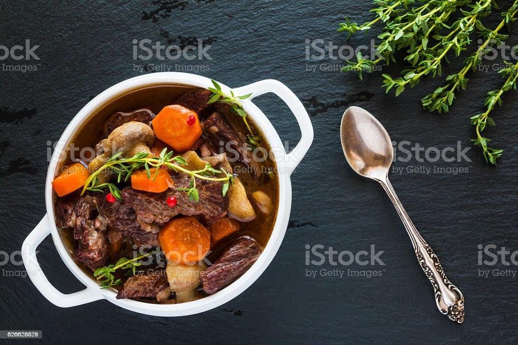 Beef Bourguignon in a white soup bowl on black stone stock photo