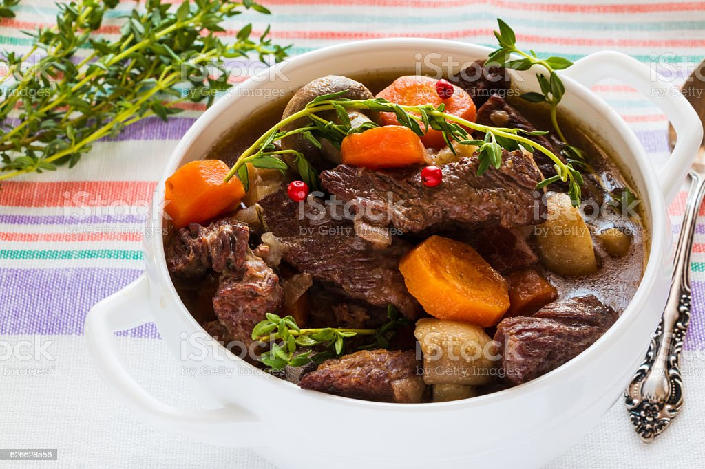 Beef Bourguignon in a white soup bowl. Stew with carrots, stock photo