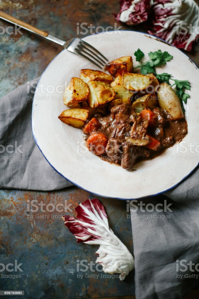 Beef bourguignon in ceramic plate with baked potatoes stock photo